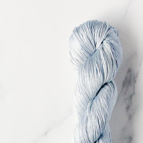 Pale blue silk yarn skein detail shot on a white marble backdrop.