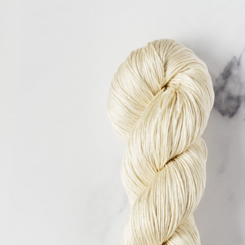 Detail shot of a pastel yellow silk yarn skein on white marble background.