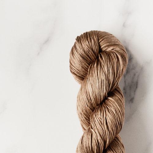 Detail view of hazel brown silk yarn skein on white marble background.