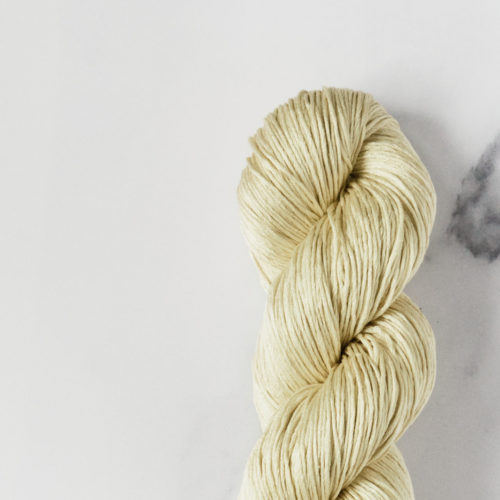 Detail shot of a soft yellow silk yarn skein on white marble background.